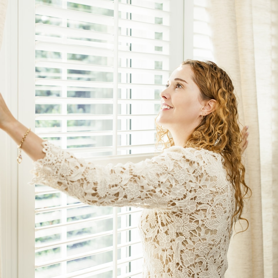 Women putting up window treatment for Perry Homes May blog.