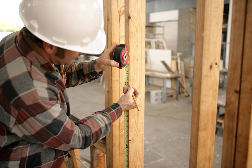 A construction electrician measuring up 48 inches to install a switch box. Model is a licensed master electrician. All work being performed in compliance with code and safety regulations. Utah home builder.