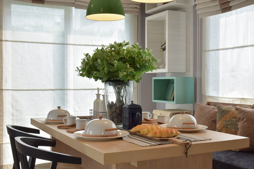 Utah home builder Breakfast setup on wooden table with nice vase and modern chair