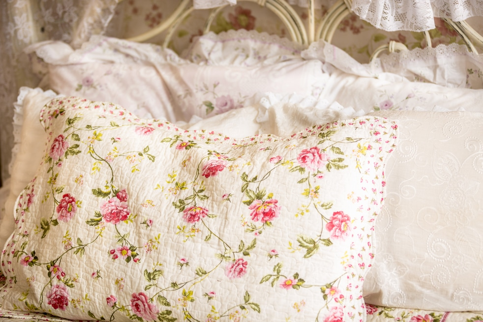Utah home builder Closeup photo of pillow with floral print on big bed