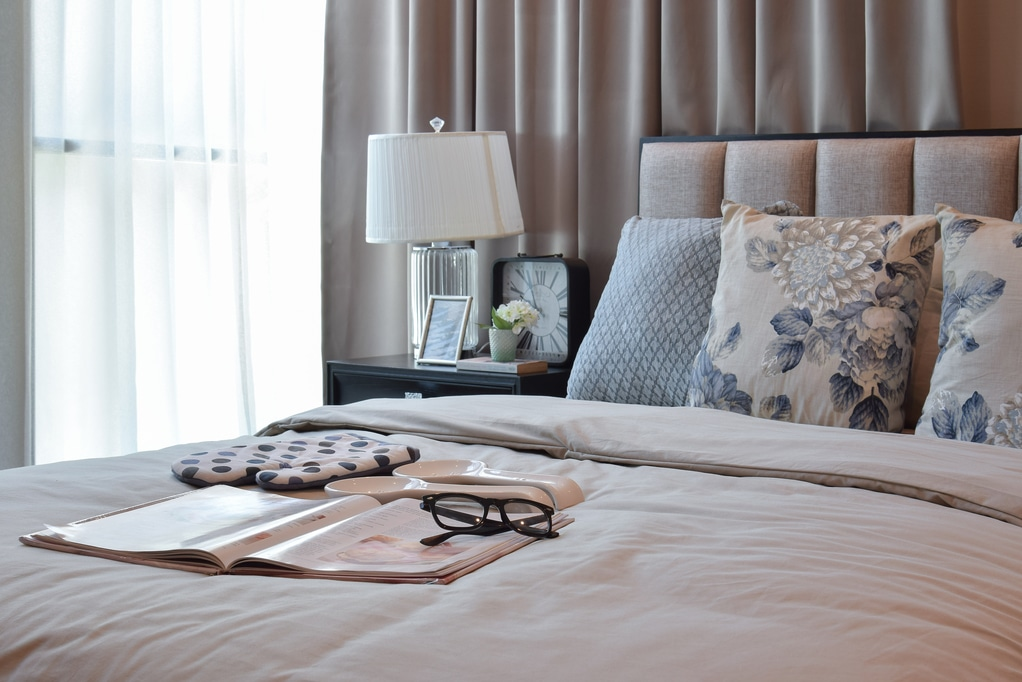 Utah home builder elegant bedroom interior design with floral pattern pillows on bed and decorative table lamp.